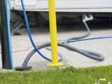 Some campsites have full-service pitches – here, waste water is carried from the caravan using a long hose