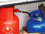 A cylinder-mounted butane regulator is blue, propane is red