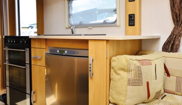 The nearside galley kitchen is well-equipped, with ample worktop and storage, and essential appliances