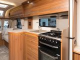 The kitchen has a circular cupboard, an oven and grill, and a dual-fuel hob