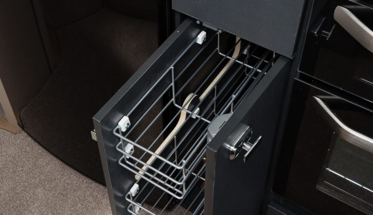 The kitchen has practical pull-out wire baskets and a large cutlery drawer