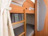 Bunk beds run across the rear of the van, a fixed ladder giving access to the upper one