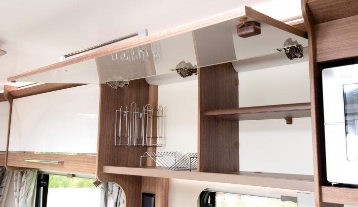 The large latched kitchen cupboard in this Bailey caravan is shelved and has handy crockery racks