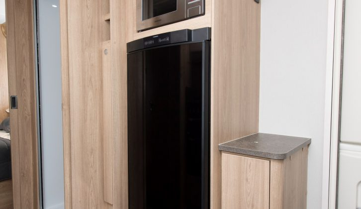 On the nearside, opposite the main kitchen, is a 155-litre fridge with a microwave above