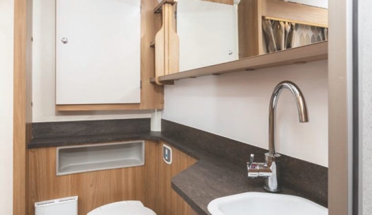 There is a spacious washroom with smart handbasin, swan-neck tap and lots of cupboard space